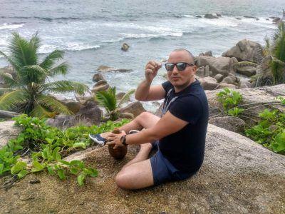 Stephan versucht einen Kokosnuss zu öffnen auf La Digue Seychellen